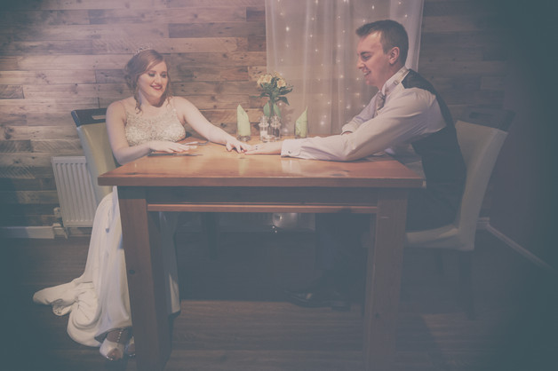 Bride and Groom holding hands across a table.