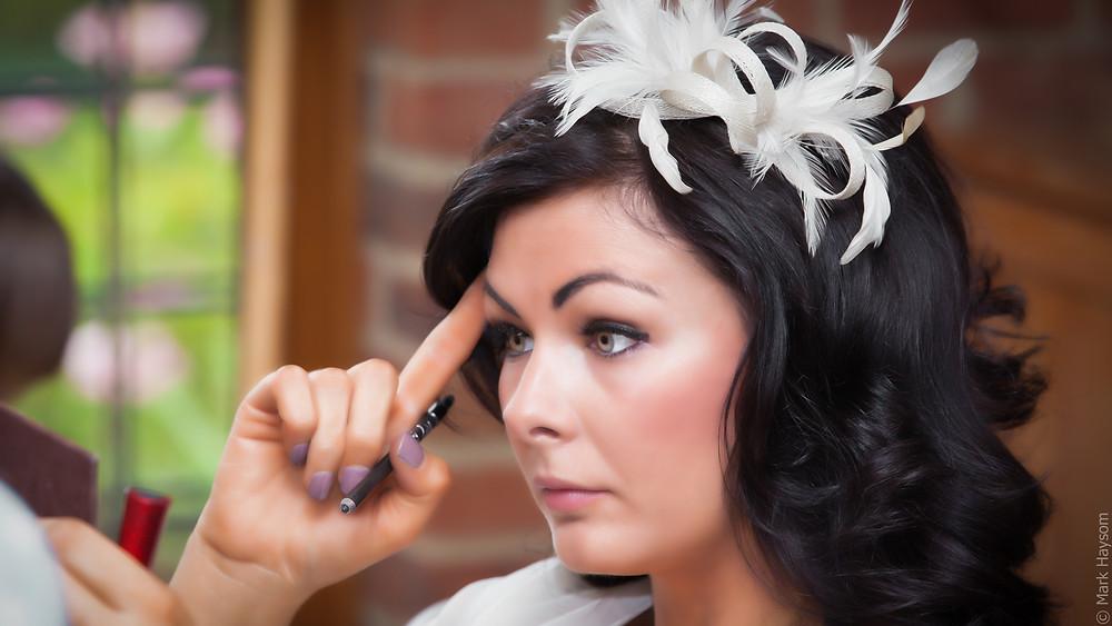 Bridesmaid putting on eye makeup.