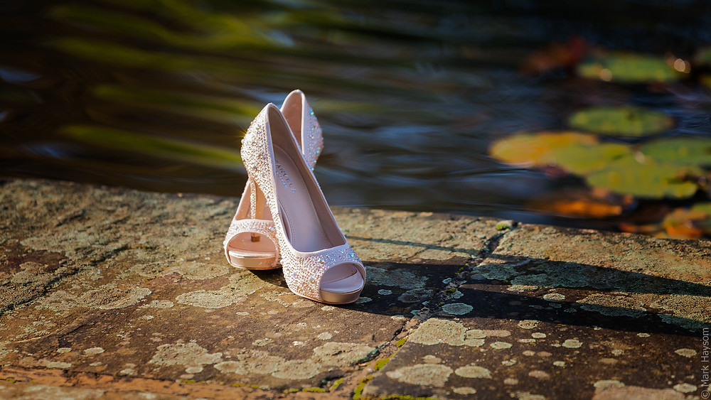 Brides wedding day shoes by a pond.