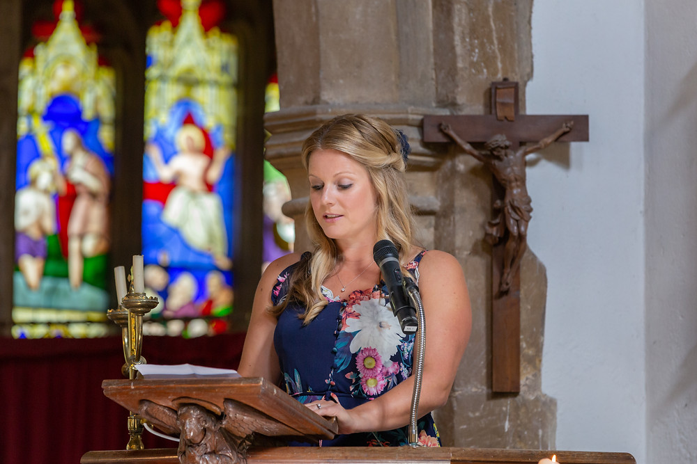 Wedding guest giving a reading in an old English church.