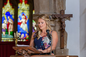 Wedding Day guest giving a reading in an old church with stained glass windows in the background.