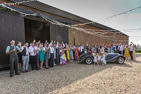 Wedding Day group shot with a Morgan sports car at Eastfields Farm Barns Bedfordshire.