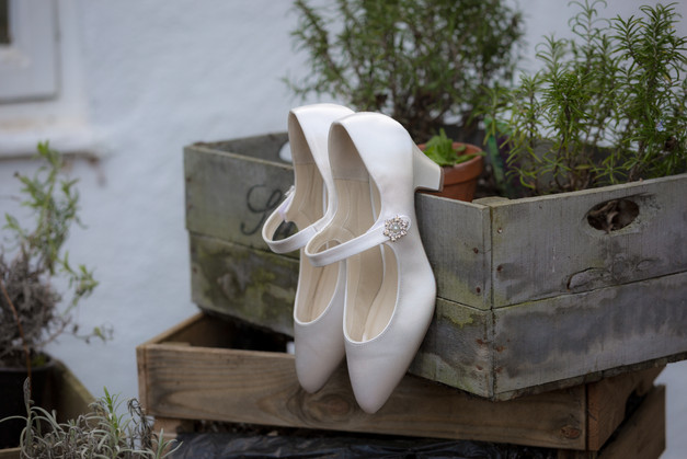Wedding day shoes hanging from a flower box.