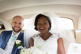Happy married couple in their wedding day car.