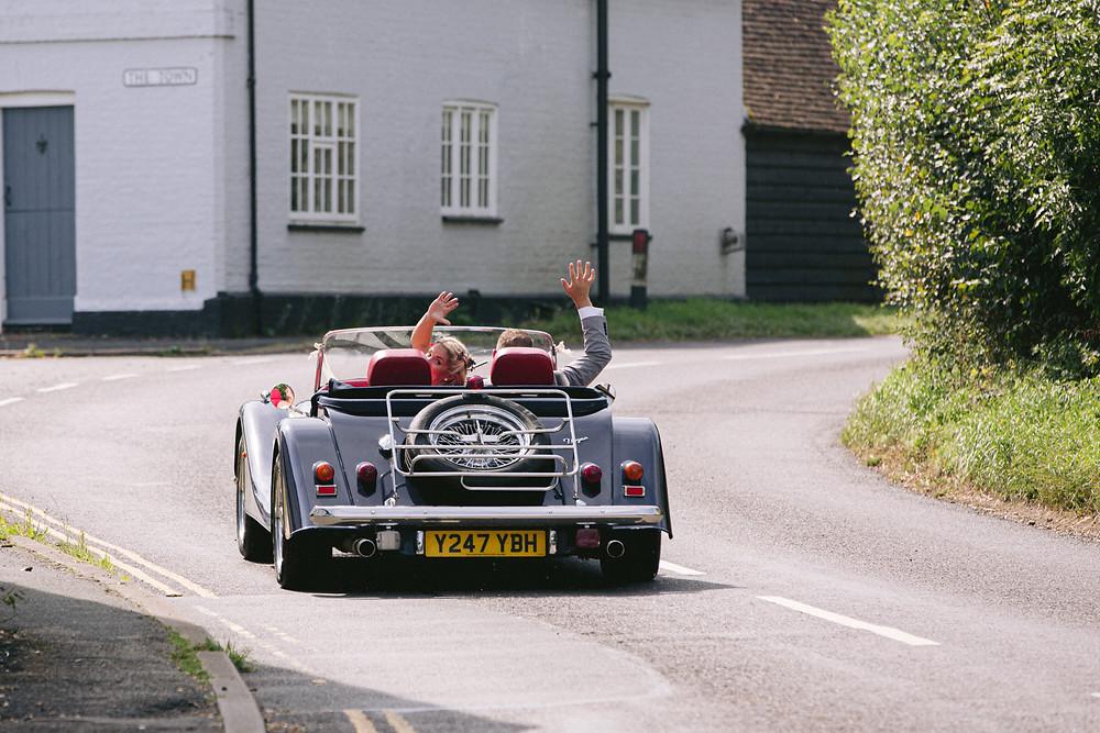 Bride & Groom waving goodbye in a Morgan sports car on their wedding day.