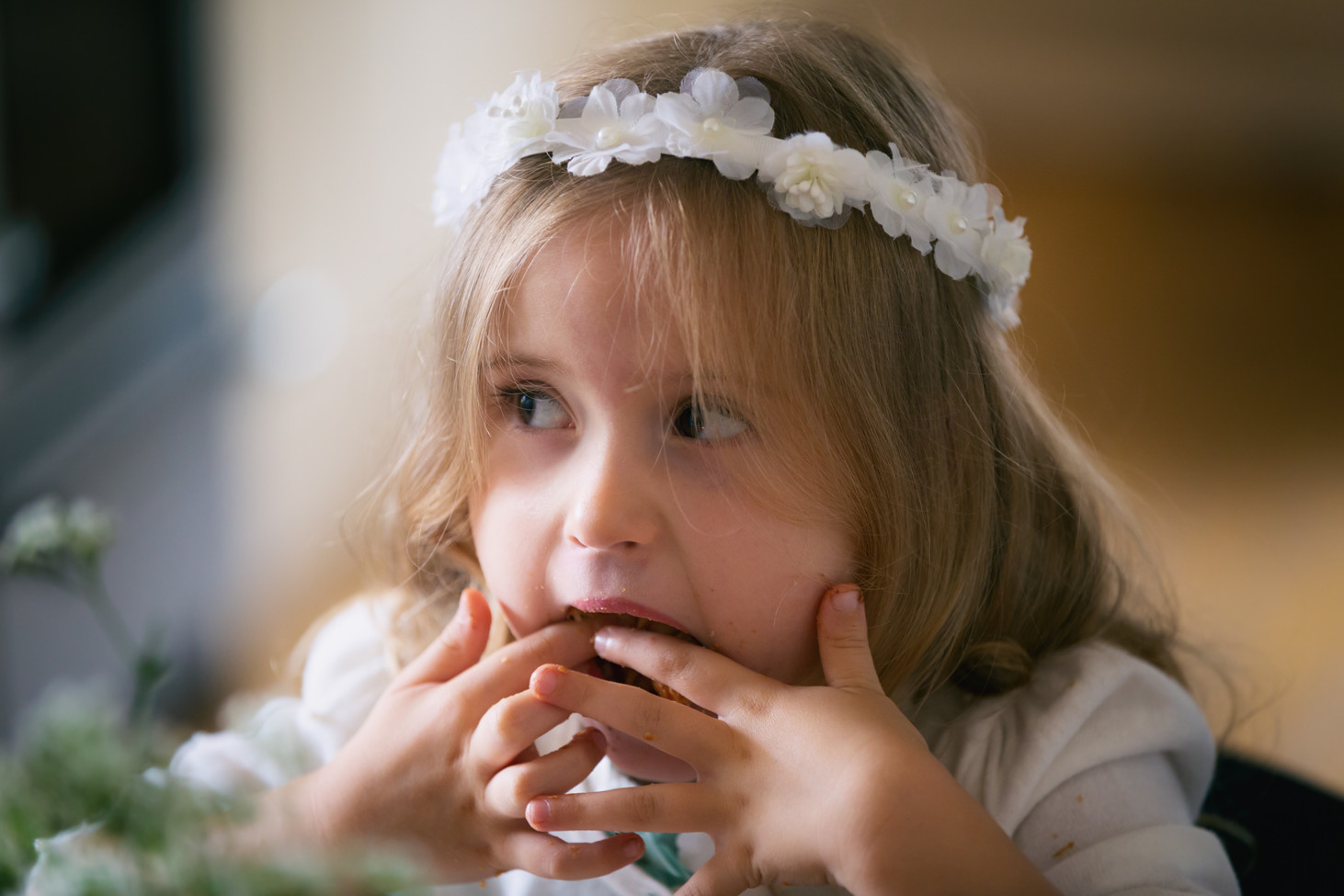 Flower girl shoving food into her mouth.