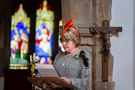 Mother of the Bride giving a wedding day reading in an old church with stained glass windows in the background.