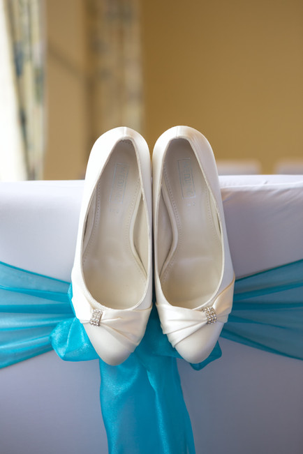 Wedding day shoes hanging from a chair with a blue ribbon.