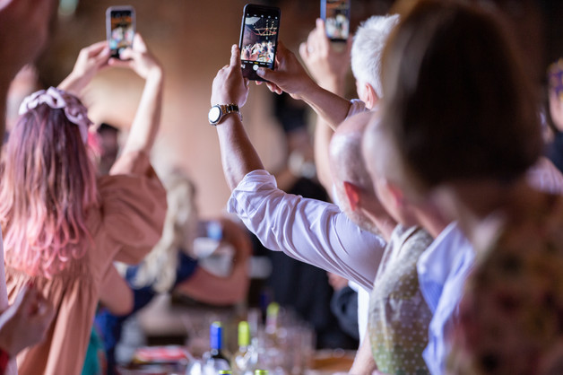 Wedding guest taking pictures with their mobile phones.