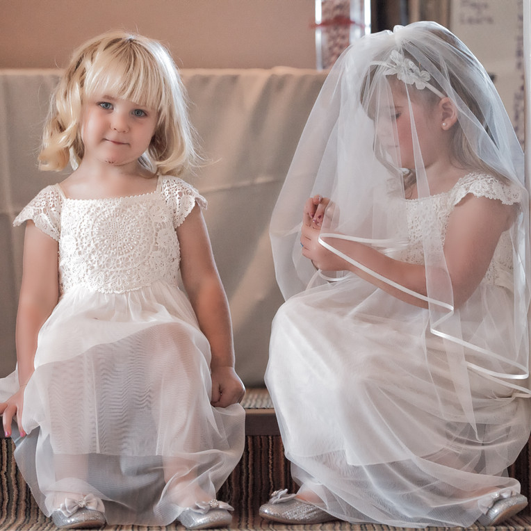 Two flower girls sat at the top of the srairs with the Brides vale.