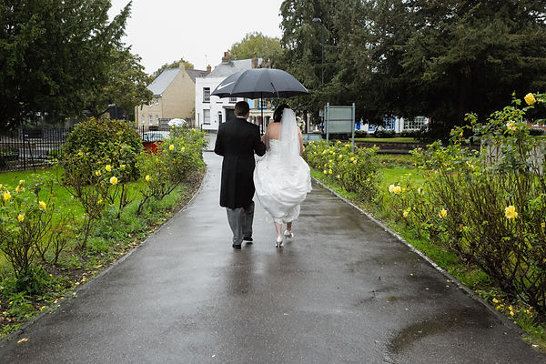 Bride and Groom walking away from the church in the rain with a black umbrella.