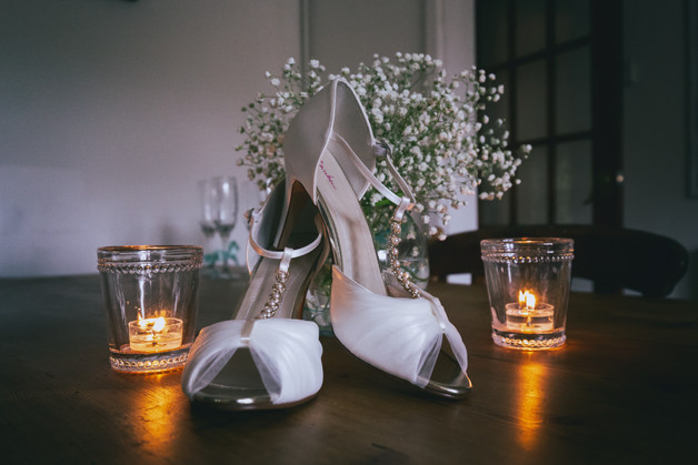 Brides wedding shoes lite with candle light.