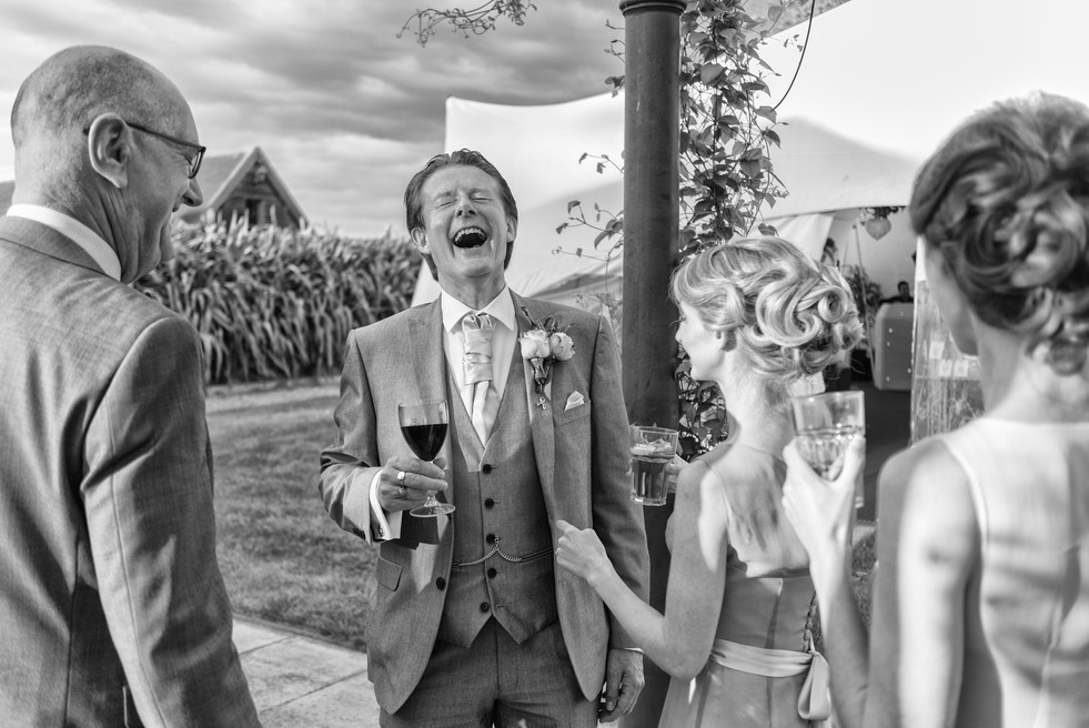 Father of the Bride with the Bridesmaids laughing whilst drinking a glass of wine.