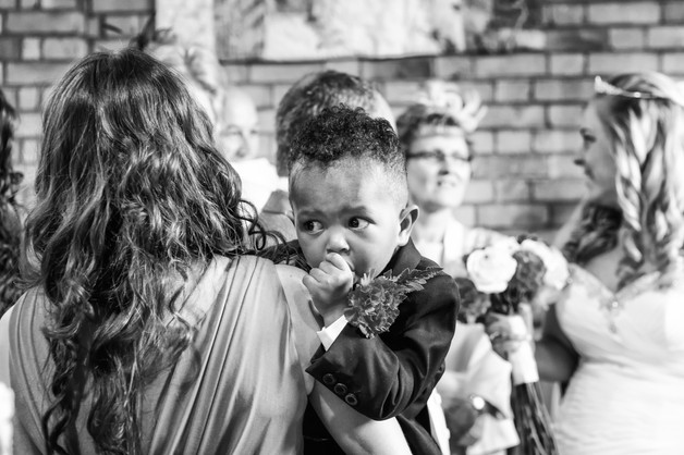 Bridesmaid holding the pageboy who is sucking his thumb.