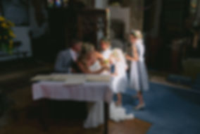 Married couple with their young children signing the registry book in an old church with sunlight streaming in.