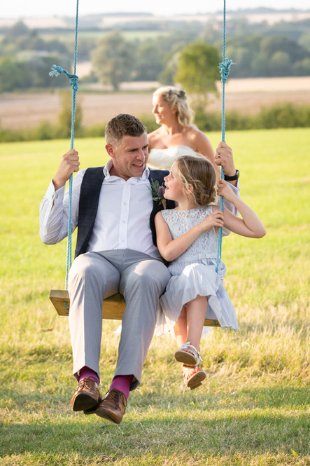 Groom on a swing with his daughter being pushed by the Bride.