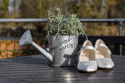 Watering can and wedding shoes.