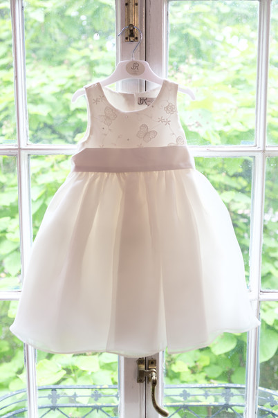Flower girls dress hanging in the window.