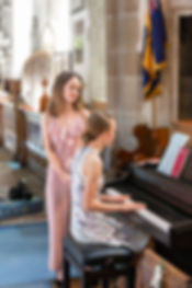 One young lady playing the piano whilst the other young lady sings in a church during a wedding ceremony.
