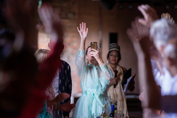 Wedding guest saluting and waving at the guests whilst taking a picture on her mobile phone.