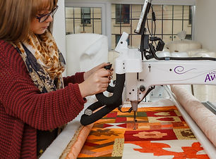 Young lady using an automated embroidery machine to fashion a quilt.