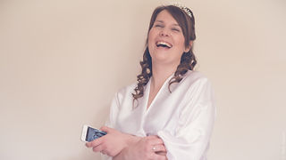 Laughing Bride in her dressing gown holding her mobile phone.
