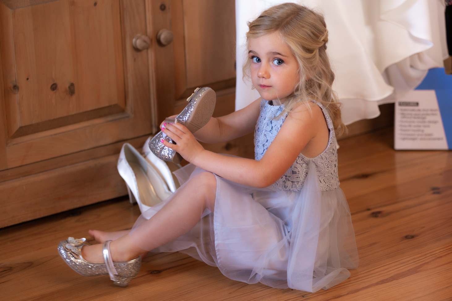 Flower girl putting on her sparkly shoes.