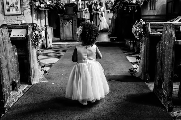 Flower girl dropping petals in the church.