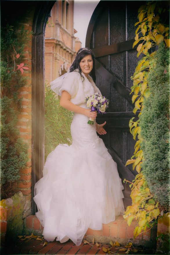 Bueatiful Bride standing in a old garden with a wooden door.