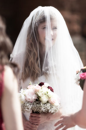 Beautiful Bride holding her bouquet waiting to enter the church to get marred.