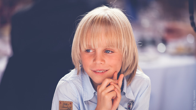 Young lad with blonde hair smiling.