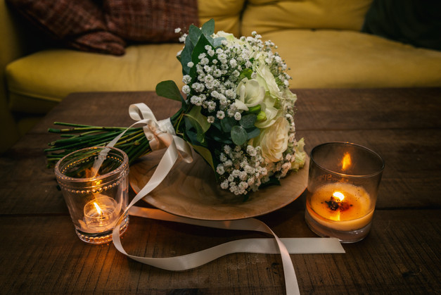 Brides bouque with candles by the side.