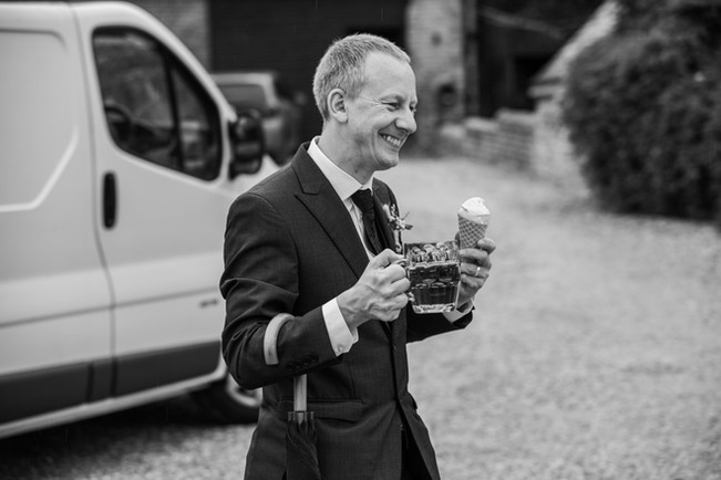 Best man with an umbrella, pint of beer and an ice cream.