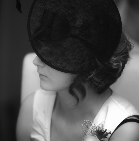 Wedding day guest in a lovely hat, pictured in portrait mode.
