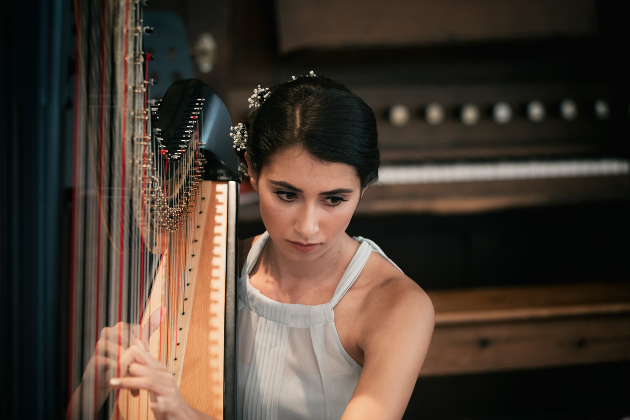 Young lady playing the harp in a church setting.
