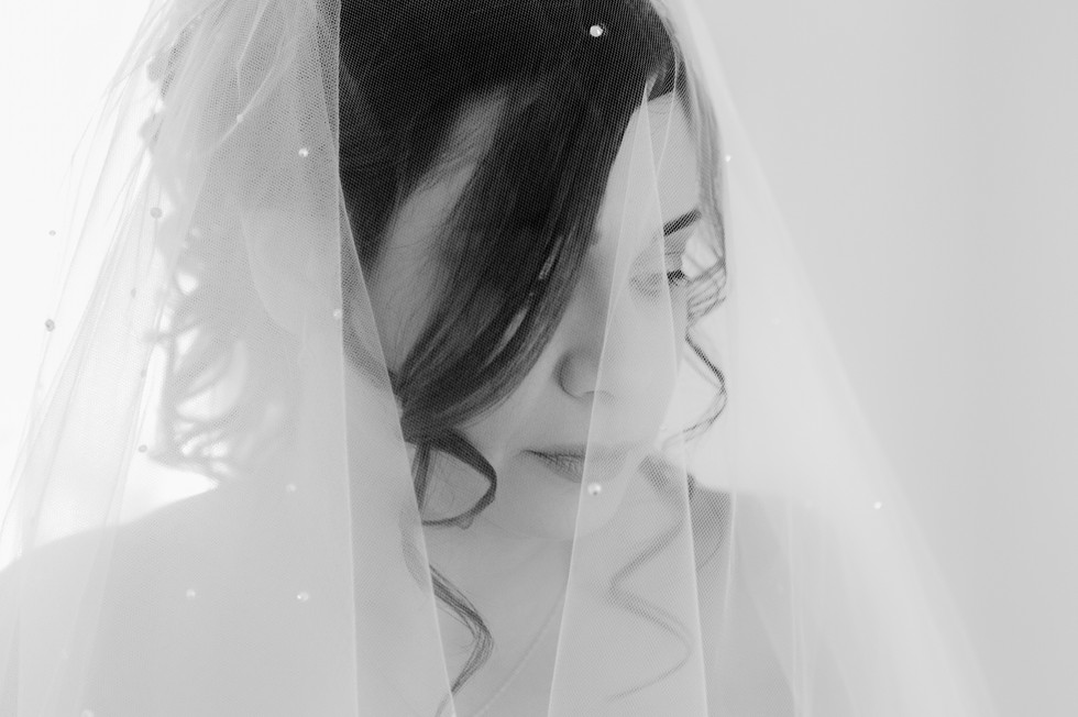 Bride in her wedding dress and veil deep in thourght.