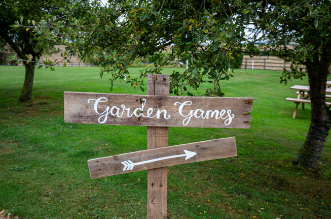 Wooden sign pointint to Garden Games.