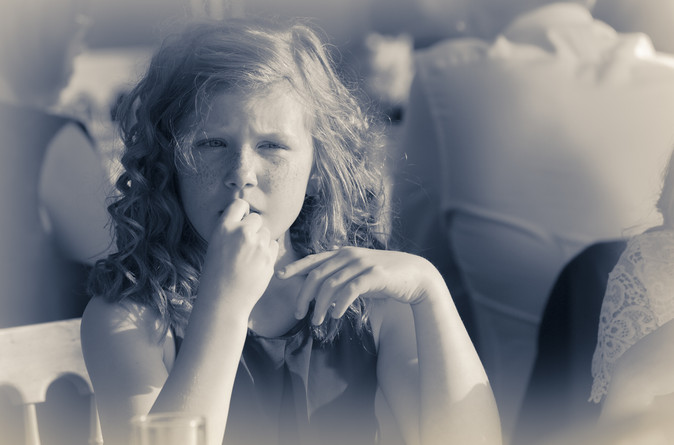 Young girl touching her face and looking deep in thourght.