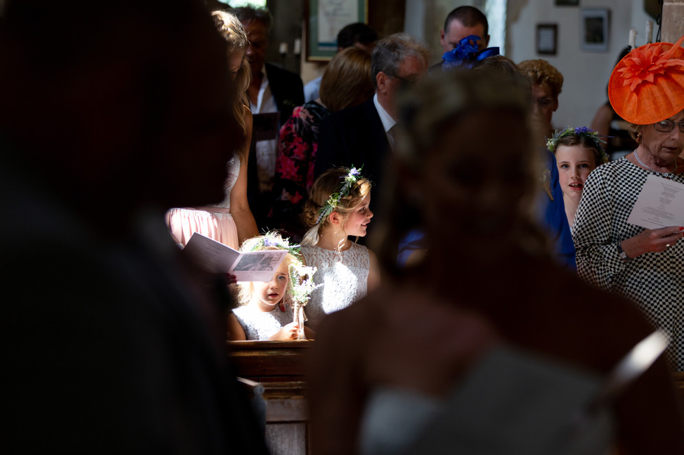 Flower girls in a church with sunlight streaming down on them.