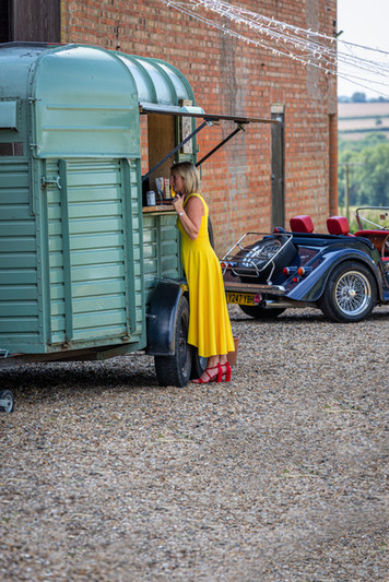 Wedding guest visits the Horse Box mobile bar in a yellow dress and red shoes.