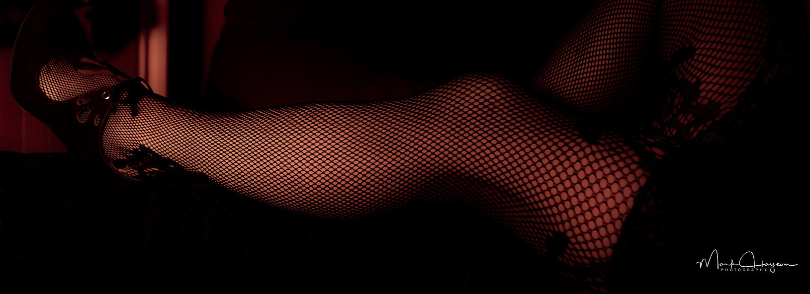 Women with fishnet stockings and little black dress on a couch in a dimly lit room.