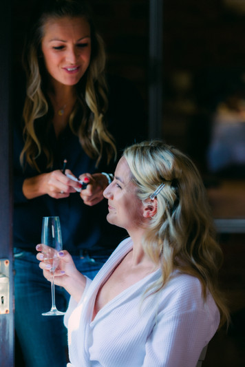 Bride getting ready with a glass of champaign.