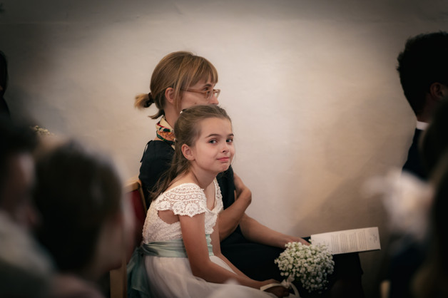 Flower girl in an old English church smiling and looking into the distance.