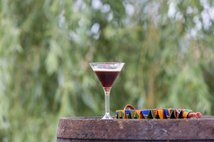 A cocktail on a barrel with a fan and a willow tree in the background.