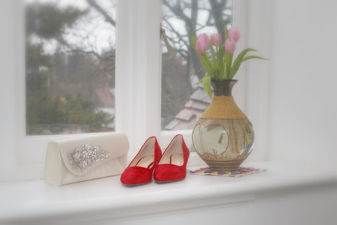 Red shoes and handbag next too a window with pink roses.