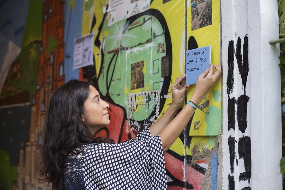 Na imagem, a artista Fernando Cardoso vestida com uma blusa preta de bolas brancas aplica um ladrilho branco com texto preto em uma parede de rua com desenhos