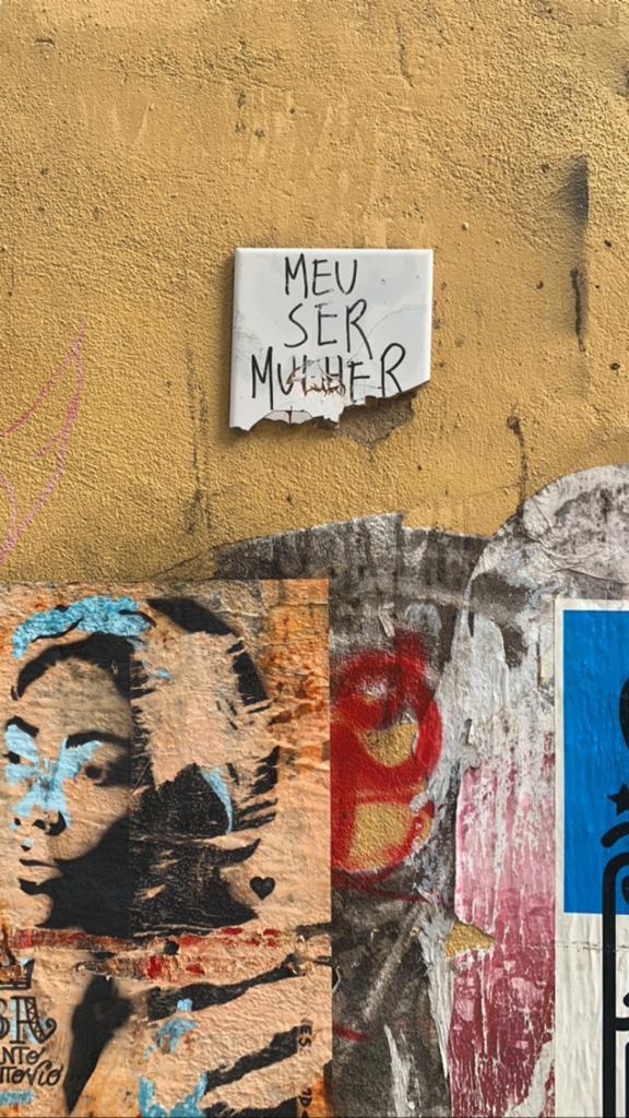 Azulejo branco com a frase MEU SER MULHER escrita com caneta preta, com a parte de baixo quebrada. O azulejo está aplicado em uma parede amarela, onde alguns outros desenhos estão colados na parte de baixo.