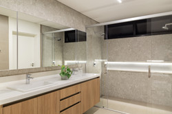 Banheiro claro com dois chueveiros e  du