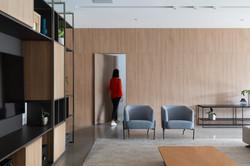 sala com painel de madeira e estante com