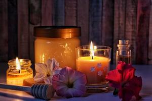 Un pot de miel entouré de bougie et de fleurs.